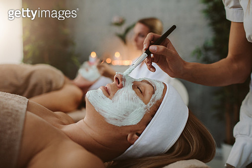 Mother and adult daughter enjoy beauty treatment in a spa center - gettyimageskorea