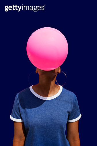 Obscured face of woman blowing balloon against blue background - gettyimageskorea