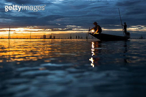 Silhouette fisherman on boat over the lake - gettyimageskorea
