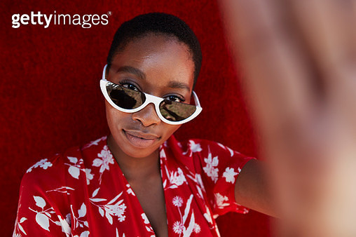 Portrait of young woman wearing sunglasses gesturing against red wall - gettyimageskorea