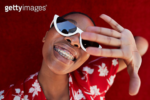 Close-up of young woman gesturing against red wall - gettyimageskorea