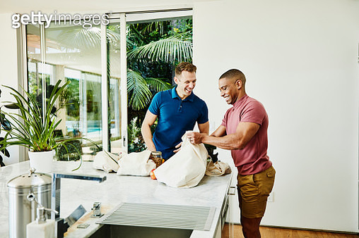 Smiling gay couple unloading groceries from canvas bags in kitchen - gettyimageskorea