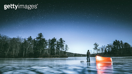 Man standing on the frozen lake in Connecticut's dark and wild north west corner of the state, next to his tent looking up observing stars on cold full moon winter night.  - gettyimageskorea
