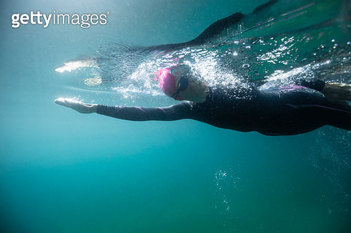 Young Woman Swimming Alone in Deep Blue Lake, Surrounded by Watery Realm of Bubbles and Light, Underwater Shot - gettyimageskorea