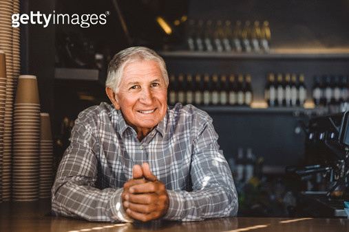 Portrait of happy senior male owner leaning at counter in cafe - gettyimageskorea