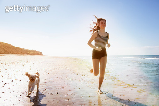 Young woman and dog running on sunny beach - gettyimageskorea