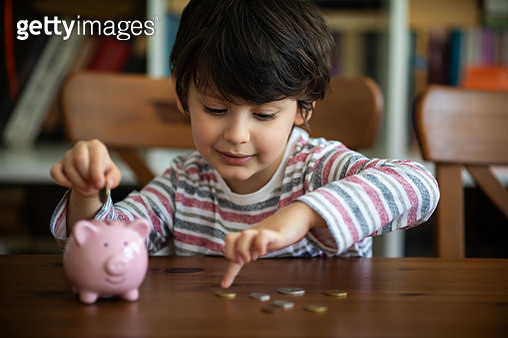 Kid put coin to piggy bank - gettyimageskorea