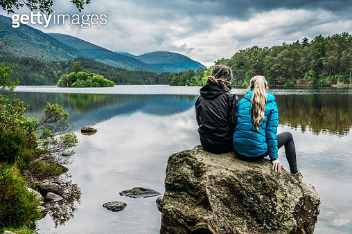 Couple sitting on rock looking at tranquil lake, Loch an Eilein, Scotland - gettyimageskorea