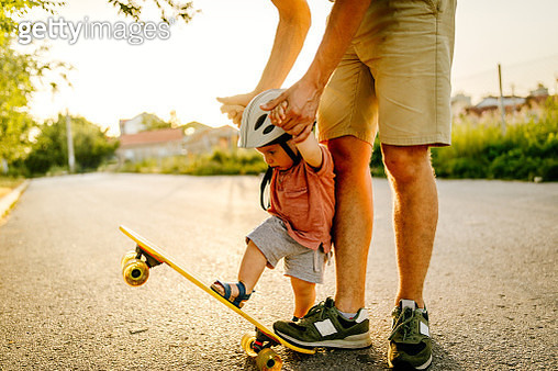 Photo of a baby boy who enjoys his first skateboard ride with a little help from his dad - gettyimageskorea