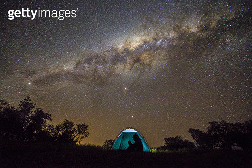Man uses smart phone in tent at night. - gettyimageskorea