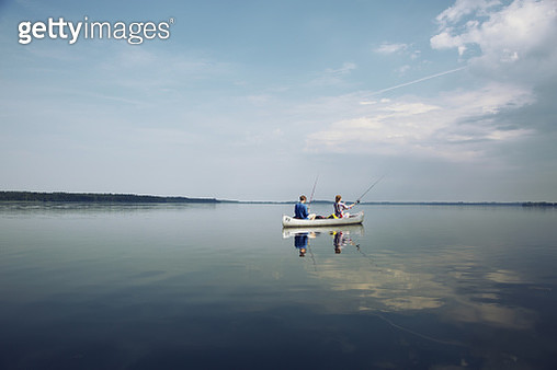 Couple fishing from a canoe on a summer day on Esrum Lake in Denmark. - gettyimageskorea