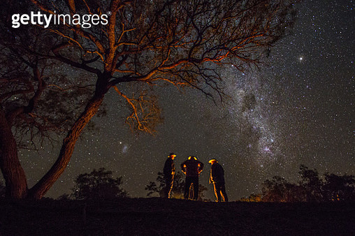 A small group of men under the stars in the Australia outback. - gettyimageskorea