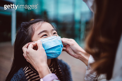 Mom helping her daughter to wear medical face mask - gettyimageskorea