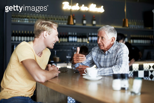 Happy father and son discussing while having coffee at cafe - gettyimageskorea
