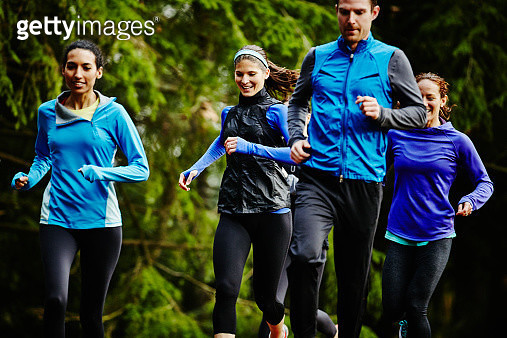 Smiling group of friends running together on trail in park - gettyimageskorea