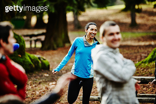 Smiling female runner stretching with friends - gettyimageskorea
