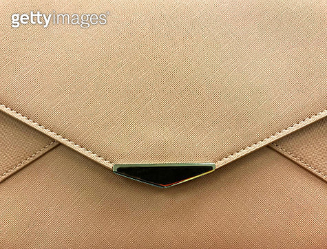Front view of a light brown purse showing edge of flap and metal decor - gettyimageskorea