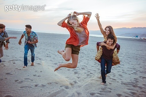 Group of friends fooling around on beach - gettyimageskorea