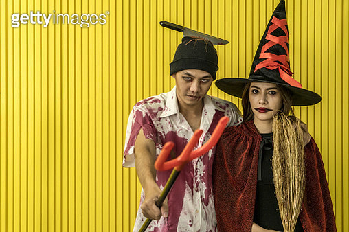 Picture of two emotional young women and man in halloween costumes on party over white background with pumpkin. Looking camera. - gettyimageskorea