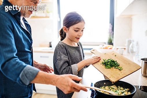 A small girl with grandparent cooking, midsection. - gettyimageskorea