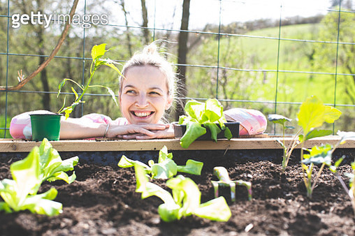 Smiling Woman Leaning On Raised Bed In Yard - gettyimageskorea
