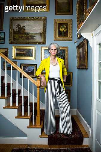Beautiful woman in a fashionable outfit with silvery, grey hair standing in a staircase with golden framed oil painting on the wall. - gettyimageskorea