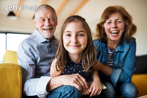 A small girl with grandmother and grandfather having fun at home. - gettyimageskorea