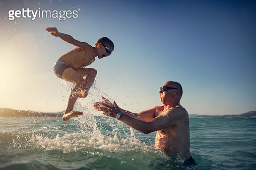 Senior man playing with grandson in sea - gettyimageskorea