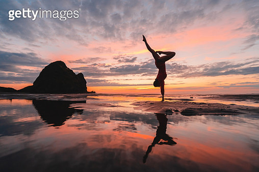 Young woman at beach standing on her hand. - gettyimageskorea