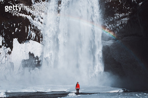 Young woman in red jacket feeling freedom and happiness staying under the big and beautiful frozen snowy waterfall during wintertime in South Iceland - Christmas in paradise - gettyimageskorea