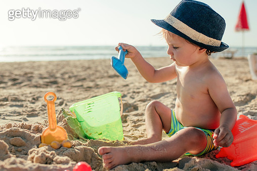 Child playing with sand in sunset - gettyimageskorea