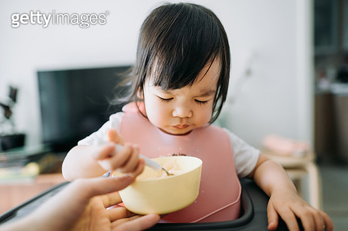 Asian toddler girl sitting on high chair feeding herself at home - gettyimageskorea