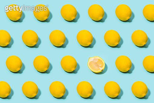 Lemon pattern with one halved, over light blue background. - gettyimageskorea