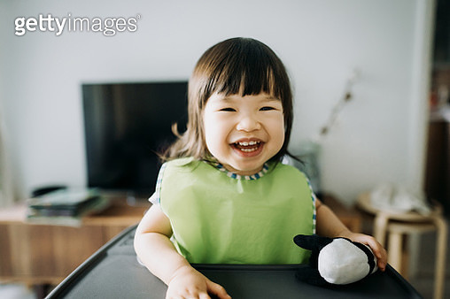 Cute little Asian toddler girl holding her favourite soft toy and smiling joyfully while sitting on a high chair at home - gettyimageskorea
