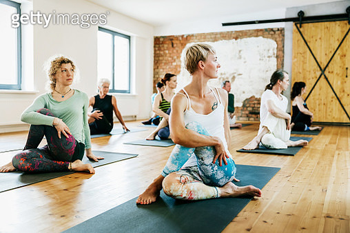 A group of friends practicing yoga together in a modern studio. - gettyimageskorea