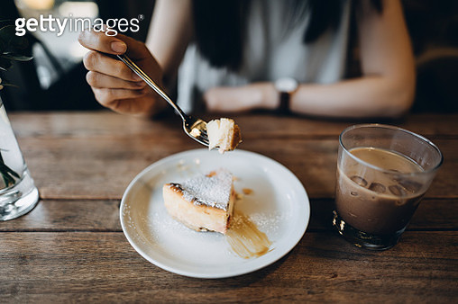 Close up of young woman having iced coffee and some sweets, a delicious cheese cake in a cafe - gettyimageskorea