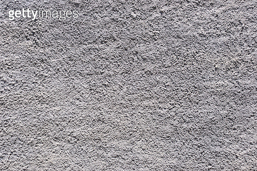 Textured plaster wall in bright sunlight in summertime. - gettyimageskorea