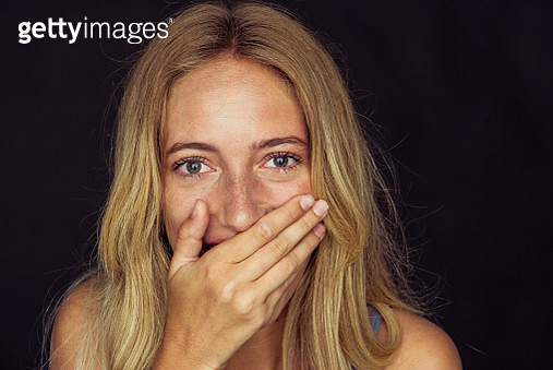 Young woman laughing with hand over mouth - gettyimageskorea