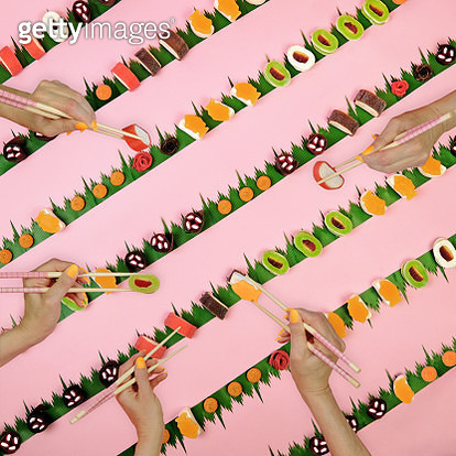 Candy sushi in a diagonal pattern on a pink background with sushi grass, chopsticks, and hands - gettyimageskorea