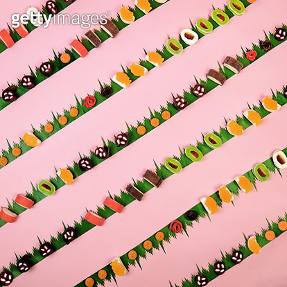 Candy sushi in a diagonal pattern on a pink background with sushi grass - gettyimageskorea