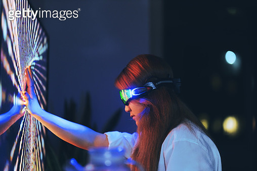 Young woman wearing augmented reality glasses touching screen with hands - gettyimageskorea