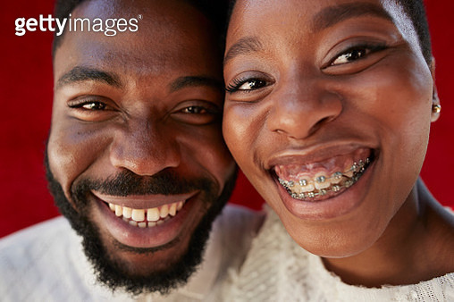 Close-up portrait of smiling young friends against red wall - gettyimageskorea