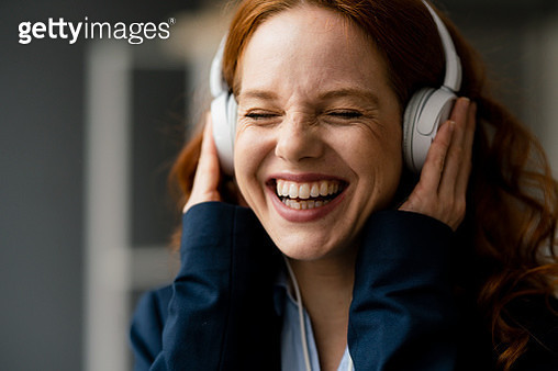 Portrait of laughing redheaded businesswoman listening music with white headphones - gettyimageskorea