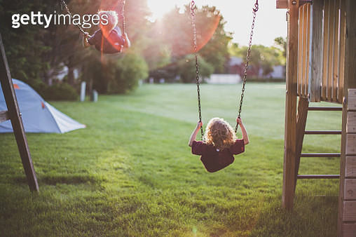 Back view of a little boy and little girl swinging high into the sky as the sun sets behind them while a tent is set up in the yard. - gettyimageskorea