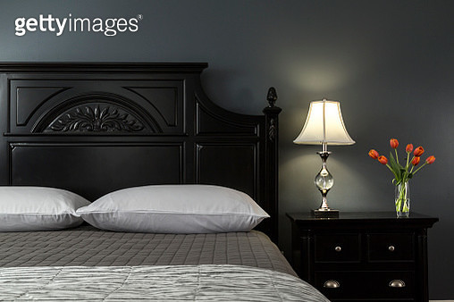 Close up of Black Painted Bed in Modern Bedroom Interior with Painted Walls of Gray and Black, Bedside Tulips in Vase - gettyimageskorea