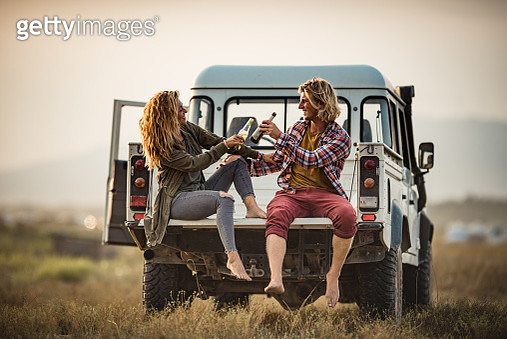 Happy couple toasting on the back of pick-up truck in nature. - gettyimageskorea
