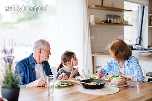 A small girl with grandmother and grandfather cooking. - gettyimageskorea