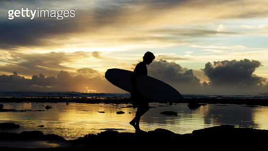 Side view of silhouette tourist with surfboard walking on shore at beach against cloudy sky during sunset - gettyimageskorea