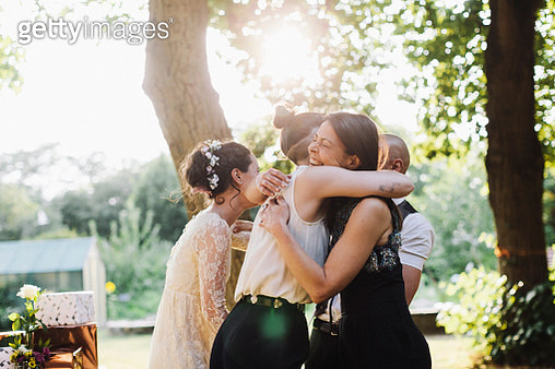 Newlywed lesbian couple being congratulated by wedding guest. - gettyimageskorea