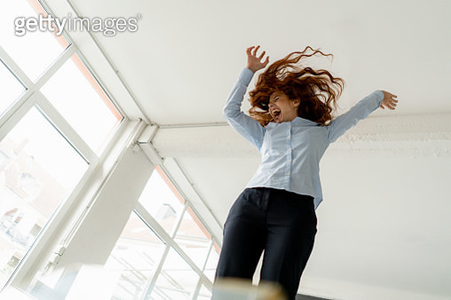 Redheaded woman standing on desk in a loft moving and screaming - gettyimageskorea